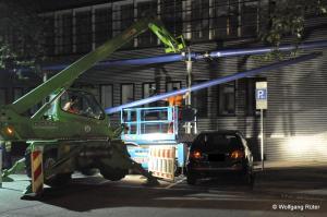 Baumaschinen harrscharf neben dem Auto und Arbeiten mit schwebender Last über dem parkenden Auto
